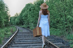 Girl in a white sundress and wicker suitcase walking on rails. Girl in a white sundress and a wicker suitcase walking on railsr Royalty Free Stock Photos