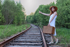 Girl in a white sundress and wicker suitcase walking on rails. Girl in a white sundress and a wicker suitcase walking on railsr Stock Images