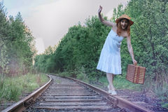 Girl in a white sundress and wicker suitcase walking on rails Royalty Free Stock Photos
