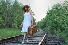Girl in a white sundress and wicker suitcase walking on rails. Girl in a white sundress and a wicker suitcase walking on railsr Stock Photos