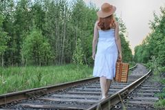Girl in a white sundress and wicker suitcase walking on rails. Girl in a white sundress and a wicker suitcase walking on railsr Royalty Free Stock Image
