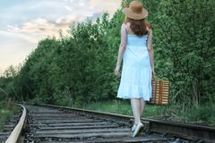Girl in a white sundress and wicker suitcase walking on rails Royalty Free Stock Photo