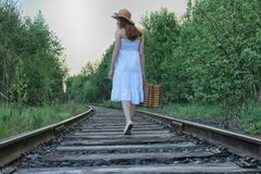 Girl in a white sundress and wicker suitcase walking on rails. Girl in a white sundress and a wicker suitcase walking on railsr Stock Photo