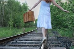 Girl in a white sundress and wicker suitcase walking on rails. Girl in a white sundress and a wicker suitcase walking on railsr Royalty Free Stock Images