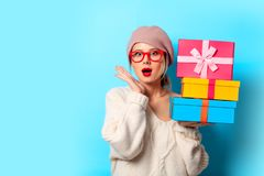 Girl in white sweater with gift colored boxes. Portrait of a young girl in white sweater with gift colored boxes on blue background stock images