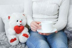Girl in a white sweater and jeans on the couch with a cup of coffee in their hands. royalty free stock photo