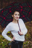 Girl in white sweater smiling with umbrella Stock Image