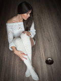 Girl with white sweater and socks is sitting on a hardwood floor with cup of coffee Royalty Free Stock Image