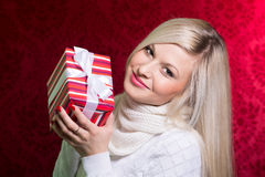 A girl in a white sweater and striped gift with white bow lookin Stock Photo