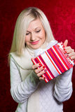 A girl in a white sweater and striped gift with white bow Royalty Free Stock Photo