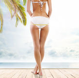Girl in a white swimsuit measuring her body Stock Photography