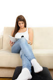 Girl in white t-shirt and jeans reading magazine on the couch Royalty Free Stock Photography