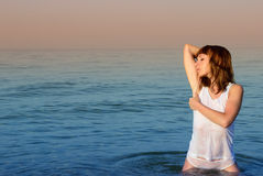 Girl in a white T-shirt and shorts in the sea Royalty Free Stock Photos