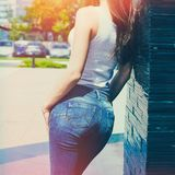 Girl in white tank shirt  and blue jeans outdoor summer day  lean on tiled wall back view stock photos