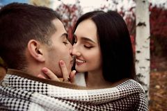 Girl with white teeth and black hair holds the guy`s face and st royalty free stock photography