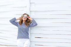 A girl in white tight jeans and sports shoes posing against a white wooden wall. In a sailor t-shirt and glasses. Curly stock photography