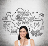 Girl in white top and business icons on concrete wall Stock Photo