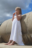 Girl in a white towel eating an apple. Young girl wrapped in a white towel eating an apple, leaning against concrete sea wall at the beach Stock Images