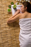 Girl in a white towel lying on spa treatments Royalty Free Stock Photography