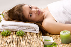 Girl in a white towel lying on spa treatments. Beautiful girl in a white towel lying on a bamboo mat. spa treatments Royalty Free Stock Photos