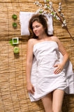 Girl in a white towel lying on spa treatments Royalty Free Stock Images