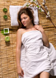 Girl in a white towel lying on spa treatments. Beautiful girl in a white towel lying on a bamboo mat. spa treatments Royalty Free Stock Photo