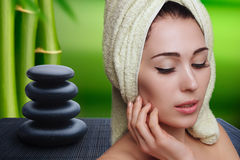 Girl in white towel turban on spa background zen stones. Royalty Free Stock Photos