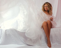 Girl  in a white transparent dress. The girl with long harmonous feet in a white transparent dress Stock Images