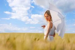 Girl with white umbrella in green field Royalty Free Stock Images