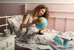 The girl in a white undershirt, sitting on a bed. Something considers on the globe.Nearby logs lie stock photo