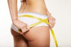 Girl in white underwear measuring her body Stock Photos