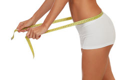 Girl in white underwear with a tape measure around her waist Royalty Free Stock Photography