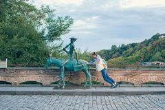 Girl in a white vest with a backpack. Next bronze donkey with a tourist Sighnaghi cohete.  Stock Photo