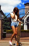 Girl in white vest and jeans shorts poses with Stock Image
