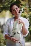 Girl and white violin. Portrait of a girl with a white violin in hands royalty free stock images