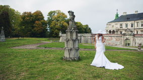 The girl in a white wedding dress near the castle. On green grass looking at the camera. RAW video record stock video footage