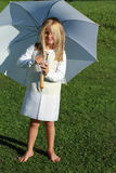 Girl in white with white umbrella. Barefoot little girl in white dress standing with a white umbrella stock photography