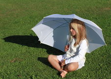 Girl in white with white umbrella. Barefoot little girl in white dress sitting with a white umbrella stock image