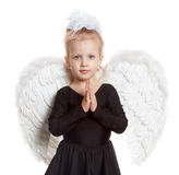 Girl with white wings in a black dress. Little girl in black dress with white wings, with her hands folded Stock Images