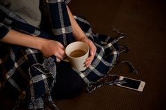 Girl whith a cup of coffee. A young girl in a plaid embrace enjoys hot coffee. waiting for the call of a loved one. photo taken by nikon d90. in 2017. before the royalty free stock photos