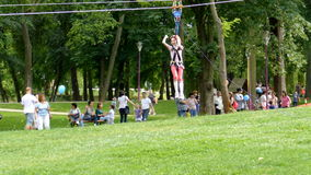 Girl who fly with a tyrolean traverse. TIMISOARA, ROMANIA - JUNE 1, 2016: Girl who fly with a tyrolean traverse in a park. International Children Day. 4K footage stock video footage
