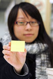A girl who is holding a yellow memo notepaper Royalty Free Stock Photo
