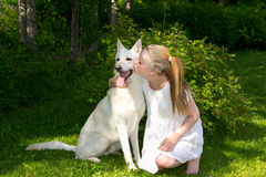 Girl who kisses her dog. Girl who kisses a dog, a beautiful summer day in nature Royalty Free Stock Image