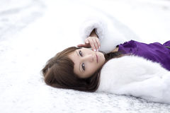 Girl who lies on the snow in  dress Stock Photography