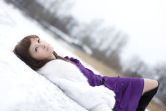 Girl who lies on the snow in  dress Royalty Free Stock Image