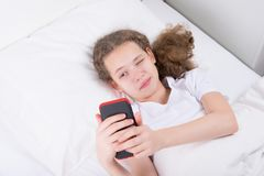 Girl who is sick and lies in bed playing in the phone stock photography