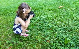 Girl who takes pictures with a photo camera in park Royalty Free Stock Images