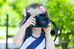 Girl who takes pictures with a photo camera in park Stock Images