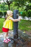 Girl who wash their hands at a fountain Royalty Free Stock Photo