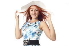 Girl in wide brimmed hat. With red hair on a white background. The wind blows her hair Royalty Free Stock Image